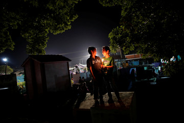 Angel de Jesus and his a brother Omar Escobar, light a candles over the grave in honor of dead relatives during the Day of the Dead celebrations in Tecun Uman