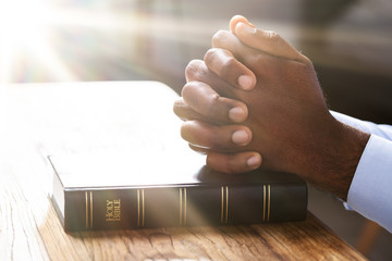 Man's Hand Over Holy Bible Book