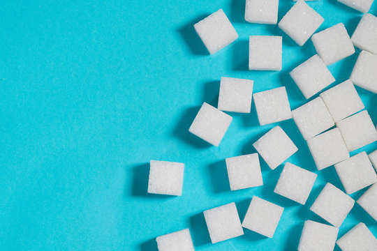 Table top shot Group of Sugar cubes vary position on light blue background