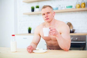 Muscular man with a naked torso in the kitchen with milk and cottage cheese, the concept of a healthy diet. Athletic way of life.