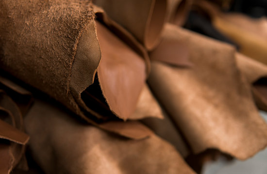 Different pieces of leather in a rolls. The pieces of the colored leathers. Rolls of natural brown red leather. Raw materials for manufacture of bags, shoes, clothing and accessories.