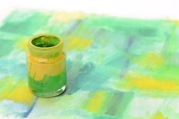Bottle of colorful paint on watercolor paper with copy space for text,art equipments concept.