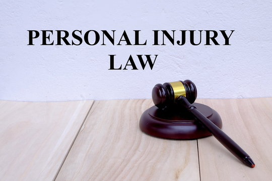 Personal Injury Law written on the wall with gavel on wooden background. Law concept.