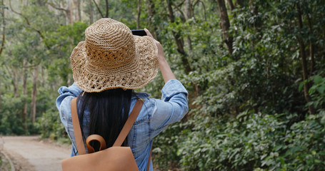 Woman take photo on cellphone when hiking