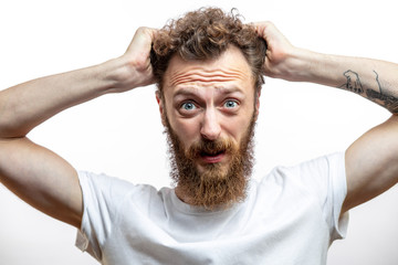 Portrait of a confused bearded man feeling fear or despair, unable to change anything, tearing his hair out , looking at camera with bugged eyes, isolated over white background