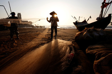 Fishermen clean their nets at a beach in Nam Dinh province