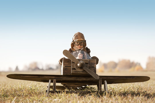 Portrait of the young aviator in a toy airplane child