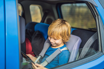 Little boy traveling on backseat of a car using touch pad to entertain himself during the trip