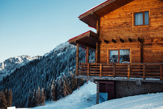 Winter vacation holiday alpine wooden house skiing relax leisure resort in the mountains covered with snow and blue sky.Dramatic cottage scene in Austrian Alps snowy panoramic landscape on a sunny day