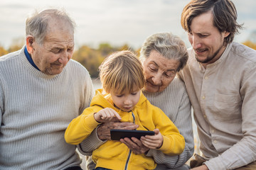 The boy shows the photo on the phone to his grandparents