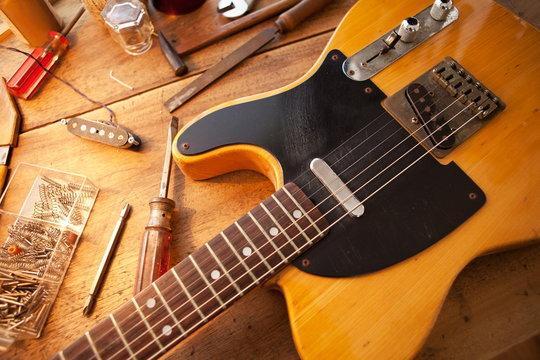 Guitar on repair desk. Vintage electric guitar on a repair work shop. Single cutaway electric guitar, amber color.