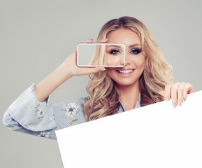 Young woman holding smartphone and showing white empty paper signboard banner with copy space  background for advertising marketing, infographics or product placement