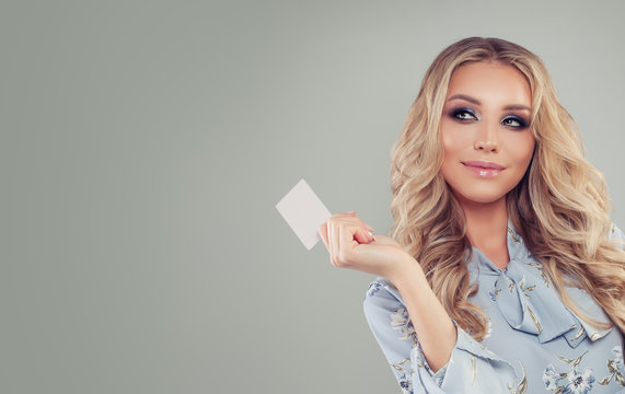 Smiling woman with credit card on gray banner background