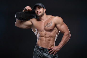 Handsome muscular male posing with cd player in front of black background