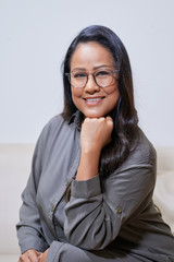 Confident adult Thai woman in gray dress and eyeglasses sitting confidently leaning on hand and smiling at camera