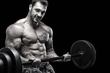 Handsome guy exercising in front of black background
