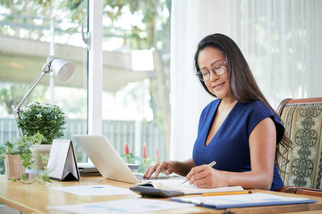 Beautiful adult ethnic woman in glasses working on laptop and taking notes in notepad sitting at table in office