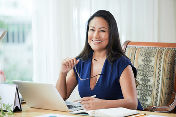 Beautiful modern Thai businesswoman sitting at table with laptop and papers smiling at camera in office