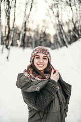 Pretty girl walking in the winter forest.