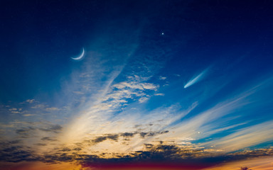 Beautiful sunset with crescent moon, glowing clouds and bright star