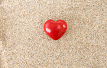Red heart, on sandy background.