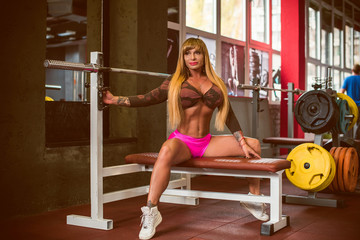 Classic bodybuilding. Muscular blonde fitness woman doing exercises in the gym. Fitness woman in the gym. Bodybuilder woman in the gym. Fitness woman on a  training