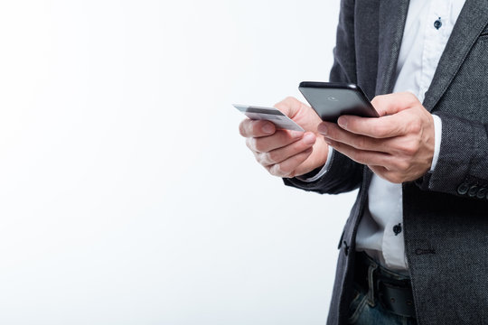 mobile payment and safe online transactions. digital finance. man holding credit card and phone.