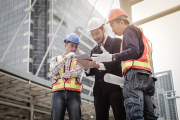 Asian engineer man and construction workers discussing on plan building project in the city