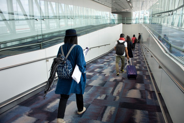 Travelers thai woman walking in terminal go to bus station at Hong Kong International Airport, Mainland China