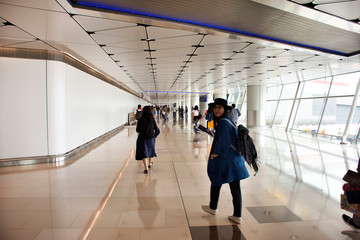 Chinese people and foreigners traveler walking in terminal of Hong Kong International Airport, Mainland China