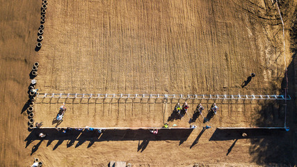 Aerial view of racers stand at the start of the motocross race