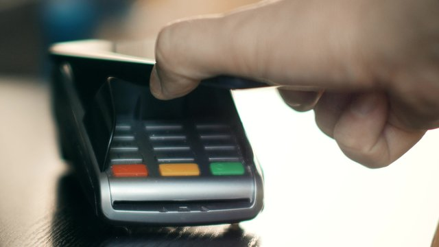 Contactless payment with smartphone with NFC technlogy. Paying with a smartphone device on a credit card POS terminal. Wireless payment.
