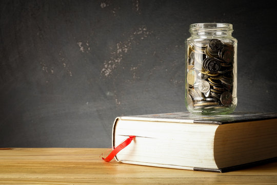 EDUCATION FUND CONCEPT with coins in a glass jar and old book.