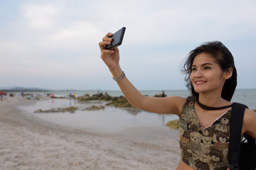 Young happy Asian woman smiling while taking selfie picture with