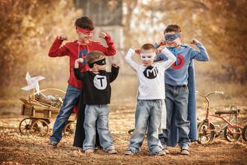 Four boys play a superhero in the playground
