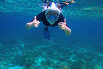 Woman underwater shows thumb up. Snorkel in coral reef of tropical sea. Young girl in full-face snorkeling mask.