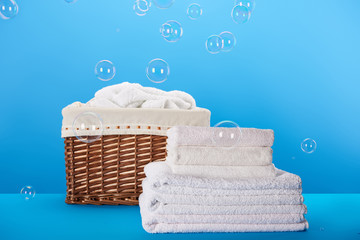clean white towels, laundry basket and soap bubbles on blue