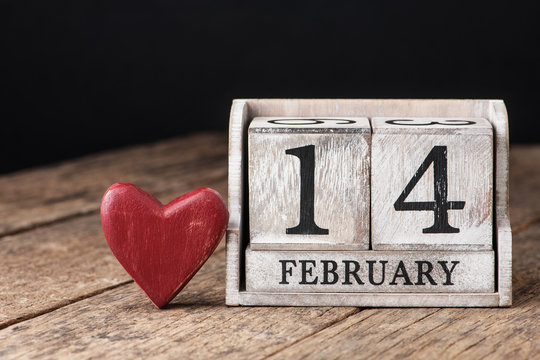 Wooden calendar show of February 14. Red heart.