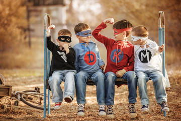 Four boys dressed as superheroes show off the power of each other