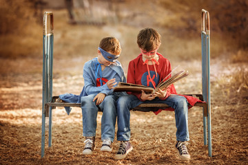 Two boys dressed as a superhero looking photo album in a garden