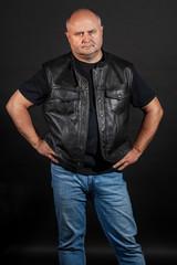Adult brutal bald man in a leather jacket, dark background