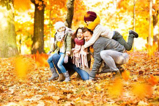 Happy Familiy in Sunny Autumn Landscape