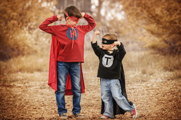Two boys play a superhero in the playground