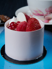 White chockolate cake with strawberies, raspberries and redcurrants served on a blue plate