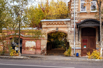 View of an arch of an entrance to a court yard of the ancient brick house in the autumn afternoon.