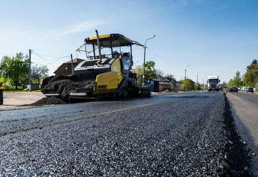 Worker operating asphalt paver machine during road construction and repairing works. A paver finisher, asphalt finisher or paving machine placing a layer of asphalt. Repaving