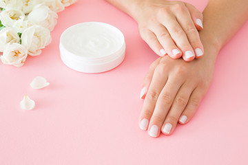 Cadres-photo bureau Spa Young, perfect, groomed woman's hands using moisturizing herbal cream. Care about nails and clean, soft, smooth skin. Manicure, pedicure beauty salon. Beautiful roses on the pink table. Fresh flowers.