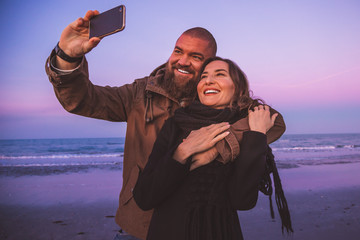 Young couple taking a selfie with a smartphone on the beach at sunset (blue hour). Lovers on a date having fun and smiling. White teeth smile concept.