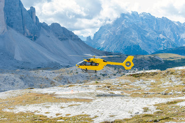 Yellow helicopter in flight, Dolomites, Italy