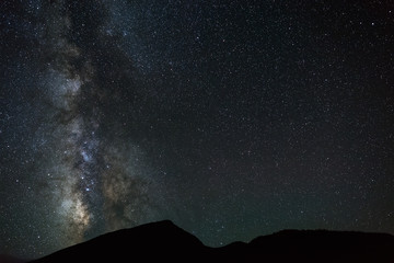 The bright stars of the Milky Way in the night sky over the mountains of the North Caucasus.